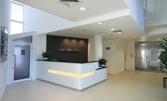 Reception Area, reception desk with slot light feature in paneled white glass front with black composite counter top, limestone floor tiles, Grey feature wall covering with brushed stainless steel building signage, painted white walls & plasterboard ceiling.
