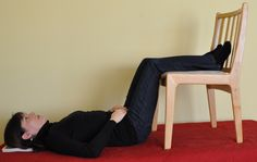 Lie down with legs resting over a chair to ease back pain.