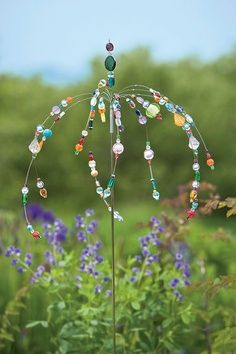 """Bead sparklers"" for the garden. Strung on wire, stuck into cork of a wine bottle, that's filled w/pebbles or colored sand to weigh it down. Pretty & easy!"