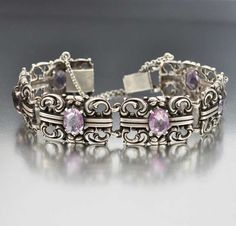 Sparkling natural amethyst gemstones glisten in this transitional Art Nouveau to Art Deco era silver bracelet. Each gently curved link has an elaborate Nouveau scroll design centered with an open back