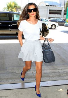 Keeping it cute and casual: Cheryl Cole looked effortless stylish in a white T-shirt a short grey A-line skirt a and a pair of blue heels as she arrived at LAX