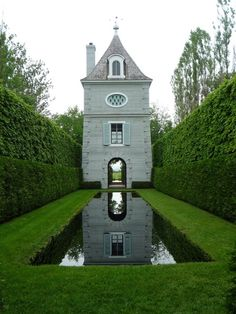 View of the pigeonnier from the reflection pool at The Gardens of Francis H. Cabot. Les Quatre Vents in La Malbaie, Quebec.