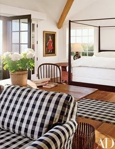 "The master bedroom ""has high ceilings and lots of light,"" Blake says. A portrait by Ammi Phillips hangs near the Vermont pencil-post bed. A lamp made from a train lantern is on the circa 1850 hutch table 