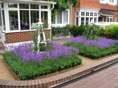 Oak obelisks with roses climbing up them, under planted with Lavender and a Buxus hedge surrounding it all.
