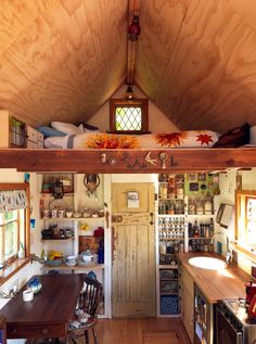 Tiny house with bathroom against back wall under sleeping loft and kitchen open to living room. Perfect design! Just needs a more elevated loft space...
