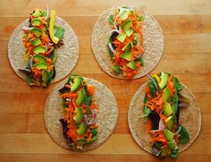 whole wheat vegetable wrap preparation - spinach mix, daiya swiss-style slices, grated carrot, red onion, yellow bell pepper, avocado, and mustard