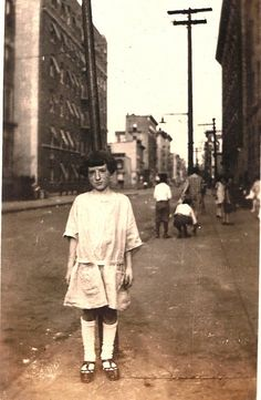 """Rose Rubin outside the family's apartment building ca 1924 in Bronx, NY. Note the street is not paved. - From comments:The boy shooting a bottle cap is playing """"scully,"""" a popular sidewalk game from the 1920s to early '40s. Winner got to keep the other boys' bottle caps for his collection"""