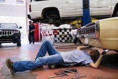 Female mechanic underneath car in auto repair shop