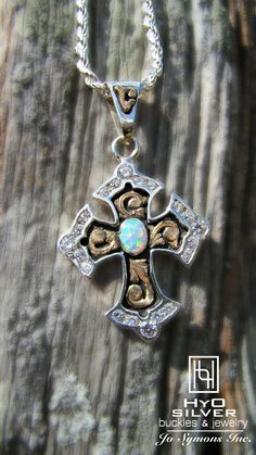 Sparkling crystals border the edge of this sterling silver cross pendant. Yellow gold overlay scrolls encase a vibrant Opal in a bezel setting, complimented by a black antique background to provide contrast for brilliant metallic hues of silver and gold. RRP013, $275.
