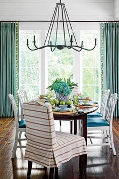 In this interior, pairing grays, blues, and pops of bright green with neutrals keeps the color scheme serene. Striped slipcovered chairs are an easy nautical touch. Blue nubbly linen curtains with pretty patterned trim are like the rest of the decor: refined but relaxed.