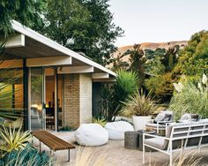 In the backyard of this Eichler home in San Rafael, California, a pair of white beanbag chairs, outdoor sofa, and chairs were sourced from West Elm and the Case Study Museum Bench is from Modernica. Photo by: Drew Kelly