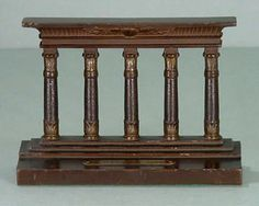 "Bookend, one of a pair, ca.1920, cast iron. The bookends are inscribed Temple of Isis on an attached brass plaque and have three steps that rise from a base  supporting five Egyptian lotus columns. The columns are topped by an entablature with a concave cornice having a central ornament of the Winged Sun, the symbol of royalty dating from the Ancient Kingdom of the Egyptians. The bookends bear the round B&H mark with printer's flowers cast into the back bottom left. Dim: H. 4"" x W. 5.87"" x…"