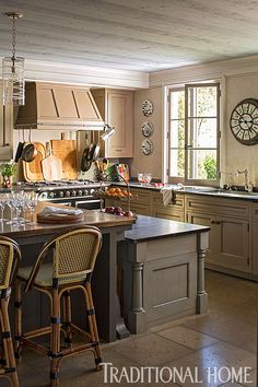 A two-level island allows space for meal prep and dining. - Photo: John Bessler and Jonathan Wallen / Design: Susan Hurwitt, Victoria Cameron, and Capucine Gooding.
