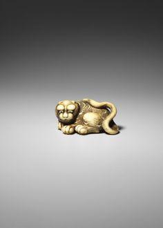Netsuke. Seated tiger. Made of ivory, eyes inlaid with ebony. Edo Period. Date: Early 19thC Production place: Osaka-fu (Asia, Japan, Honshu, Kansai, Osaka-fu) Materials: ivory ebony Technique: inlaid carved. Length: 4.5 centimetres. British Museum number: 1972,0114.19