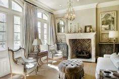 Love so drapes & windows so much. Love fireplace, tufted ottoman, chairs, table, paint color, art.