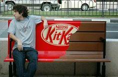 Este chico esta sentado en este banco xk ha visto q es de kitkat y se a sentado para q cuando no aya gente le pege un mordisco.