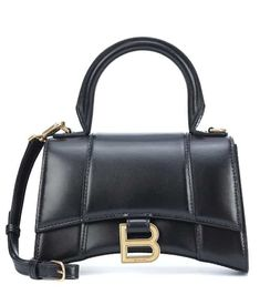 Stay ahead of the fashion curve with Balenciaga's newest it bag — the Hourglass Small tote. Crafted in Italy from smooth black calf leather, its long front flap design is secured with a vintage-effect B logo in gold-toned . Small Handbags, Black Handbags, Calf Leather, Leather Bag, Balenciaga Bag, Balenciaga Handbags, Luxury Bags, Luxury Handbags, Fashion Bags