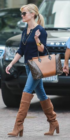 Reese Witherspoon wears a navy J.Crew shirt with Michael Kors over the knee boots and accessorizes with a Louis Vuitton bag.