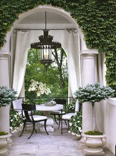 What would the less formal version of this be?  Green-covered trellis, identical topiary trees, white flowers, stone table, ivory or sage table umbrella.