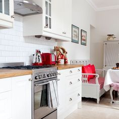 Loving this modern white kitchen with red accessories, including the gorgeous Smeg range cooker!