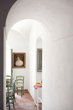 white walls with vintage portrait painting via architectural digest espana. / sfgirlbybay