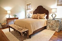 by Margaret Donaldson Interiors  Charleston, SC  A warm and inviting guest room uses soft blue and apricot as the accent colors. The headboard was custom made by a local craftsman from reclaimed wood.
