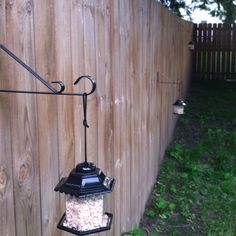 Decorate the fence using hooks and bird feeders. Simple but cute.