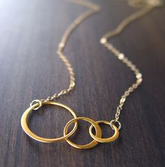 "Interlocking Circle Gold Necklace. A shiny polished style!  Pretty tripple vermeil gold circle charm is hanging from a beautiful delicate 14k gold filled chain. Each link was handcrafted into 3 different sized circles in a small to large pattern. Part of each circle is made of round wire, and was hand flattened a nice shiny polished style. Simple and sophisticated.  Charm Size: 37 x 18 x .7"" Chain Size: 18"""