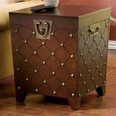 Gently spanning out from the floor, this end table features a decorative array of nailhead accents brought together in an etched lattice pattern. With a hinged top that can be easily lifted, the table