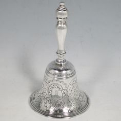 Antique Georgian sterling silver table bell having a round baluster body with hand-chased fruit and floral decoration, a cast octagonal handle, and an original silver clapper. Made by the Lias Brothers of London in 1828. The dimensions of this fine hand-made antique silver table bell are height 14 cms (5.5 inches), diameter at base 8 cms (3 inches), and it weighs approx. 225g (7.3 troy ounces).