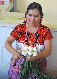 Zapotec woman sells onions and other produce at a large market in Oaxaca, Mexico