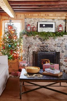 This cozy Wisconsin cabin's stone fire place gets a warm and cozy touch from a fir garland.   - CountryLiving.com