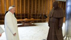 [Pope Francis stands in front of a life-sized chocolate statue of himself. The statue, made with 1.5