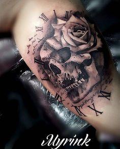 Tatuaje de estilo black-and-grey de una calavera junto a una rosa situado en el brazo izquierdo.