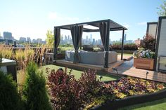 Three hole golf practice course in the foreground and a view of Chi town. Our custom pergola with laser cut design in the roof adds a nice touch to this amazing space and a Outdoor TV for those nights you want to watch the bears loose again! By: Chicago Green Design Inc.