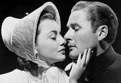 Film stars Errol Flynn and Olivia de Havilland, appearing in several movies together, are seen here embracing in one of their films in 1948....