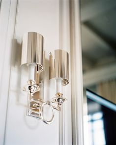A two-arm silver sconce on a white wall