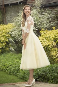 M690 - New to the True Bridesmaid Collection is this tea length dress with delicate lace bodice and full Tulle 1950's style skirt. Zip up back with buttons and elasticated buttons. Pictured here in Banana.