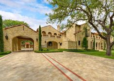 Tuscan style mansion featuring off-street parking spaces (to the right of red brick lines)