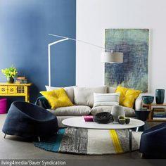 Die Sessel in Blau und das Sofa in hellem Grau mit Kissen in Gelb geben nicht nur die gemütliche Atmosphäre, sondern auch den Farbcode für das Wohnzimmer vor. …