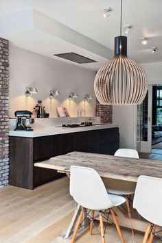 Open kitchen + dining space ; rustic wood table + Eames chair