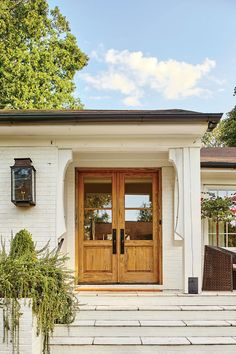 The Double Doors Warm Up The Entrance - A Dramatic Ranch House Renovation - Southernliving. The narrow single door to the entry before was hardly inviting. These new pecky cypress French doors create a more centered, visible, and welcoming first impression.