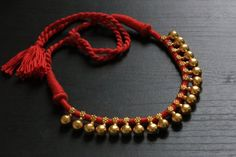 Ethnic silver replica dholki beads hand tied in red thread tassel. The necklace comes with an adjustable tassel to increase or decrease the length.
