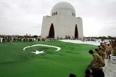 Students hold a giant representation of a Pakistani flag to celebrate the Independence Day in Karachi