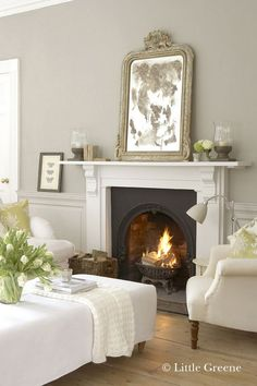 White fireplace and mirror leaning against the wall - fireplaces don't have to be large to make a warm atmosphere!
