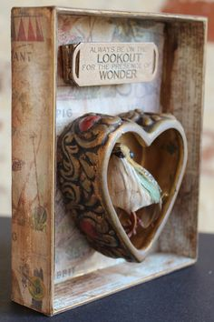 "Heart Art Shadowbox Assemblage Art - Valentine's Day - Bird's Lookout - Altered Art - Found Objects - Mixed Media. Bird's Lookout is a shadowbox that sits or hangs. Measuring 5″ high, 4.25″ wide, and 1.25″ deep, this little box is covered with an antique alphabet design paper that has been aged and embossed. Inside the box, you'll find a vintage glass heart box base which holds a little feathered bird. Above it sits a large bracelet quote charm with the words ""Always be on the lookout for..."