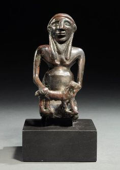 Iranian copper figurine of a kneeling sacrificium, late 3rd millennium B.C. Kerman. He wears a long loincloth and holds in front of him an animal. The clothes are regularly marked with small incisions. The face has a large nose, oval eyes and a thick mouth. He wears a long, triangular, engraved beard of streaks to point out wisps, 10.8 cm high. Private collection