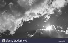 Download this stock image: in the sky the sun breaks through the clouds. Black and white photo - H7K85W from Alamy's library of millions of high resolution stock photos, illustrations and vectors.