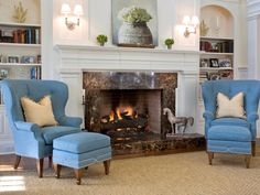 Symmetry is essential in this traditional living room designed by Jennifer Duneier. A soft blue wing chair and open shelving flank each side of the fireplace, drawing the eye toward the center of the room. The dark marble fireplace surround creates a stark contrast against the fresh white mantel.