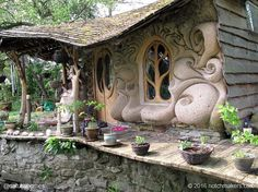 This beautiful home is a tiny sculpted cob house that looks out over the banks of a small stream.